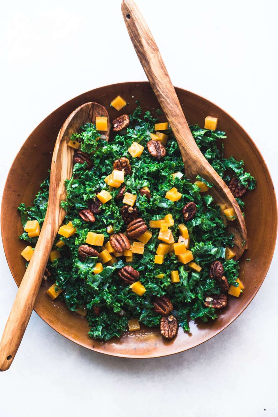 Kale and Butternut Salad in a salad bowl with wooden spoons