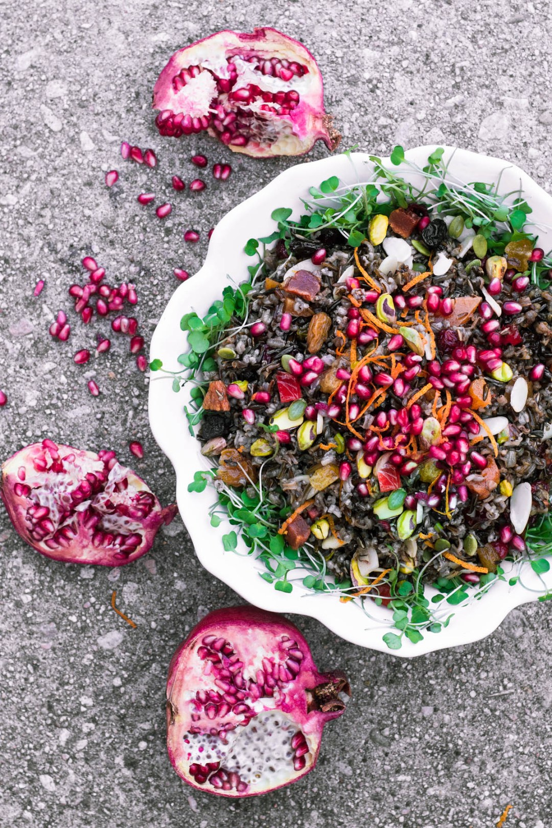 Jeweled Wild Rice in a white bowl with pomegranates