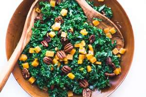 kale and butternut salad in a wooden bowl with wooden salad servers