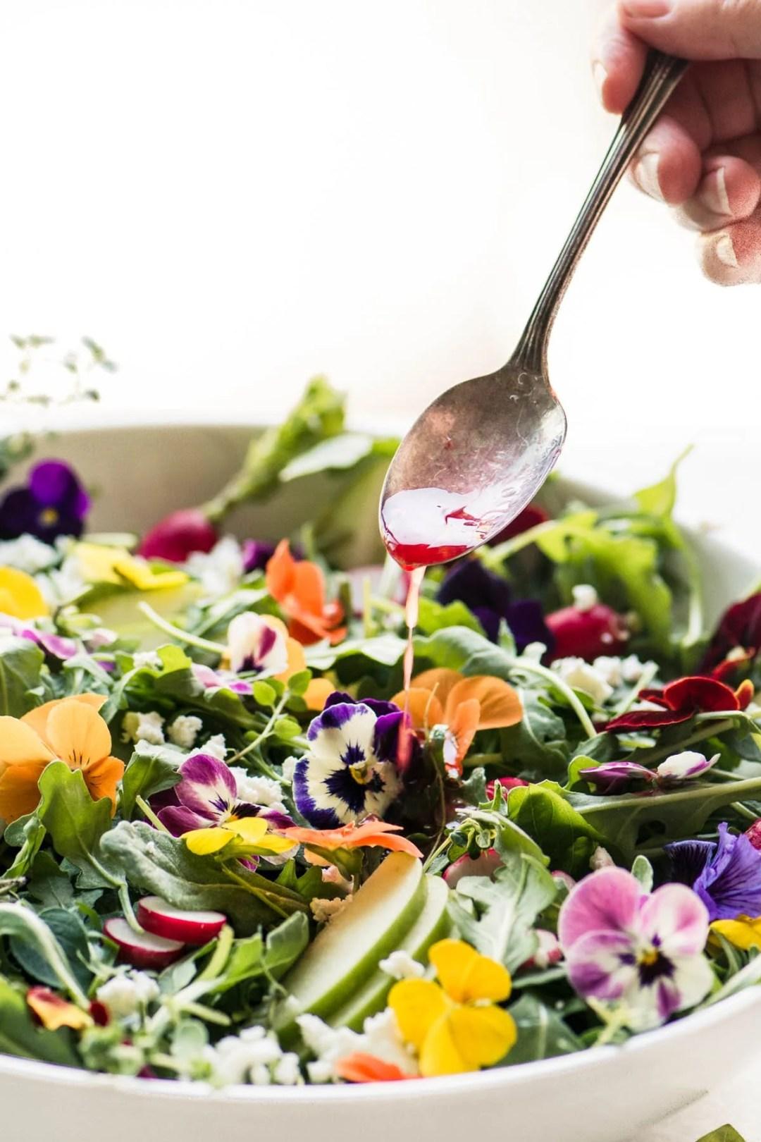 Winter Pansy Salad being dressed with blood orange vinaigrette