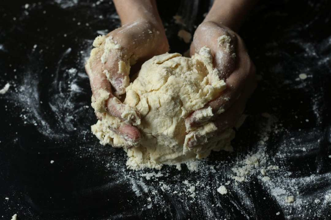 hands making pie dough on a dark ground