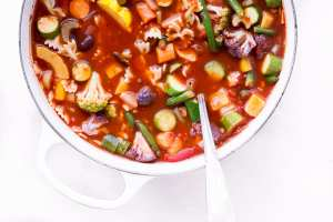 Minestrone soup in a white cast iron soup pot with ladle