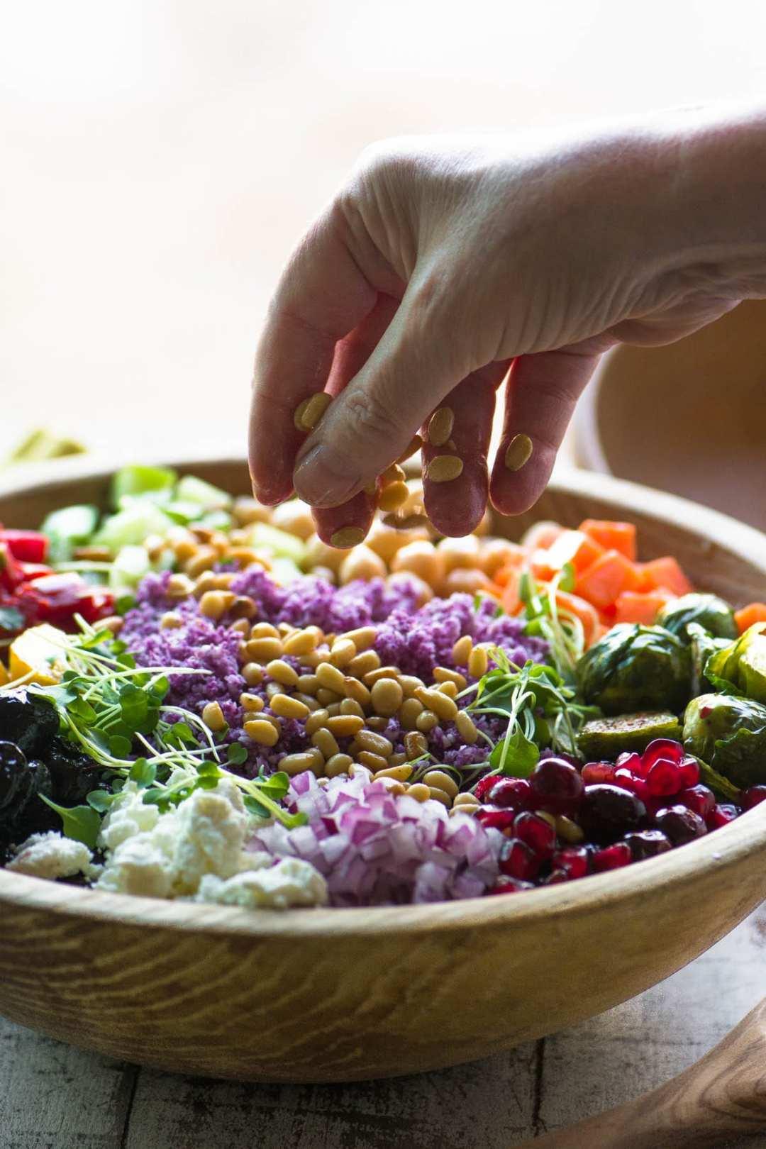 Sprinkling pine nuts onto a purple cauliflower rice salad