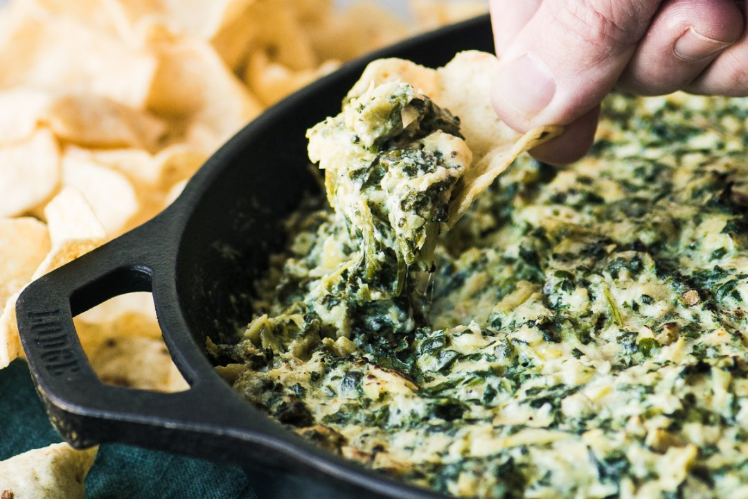 Scooping up Smokey Spinach and Artichoke Dip with a chip