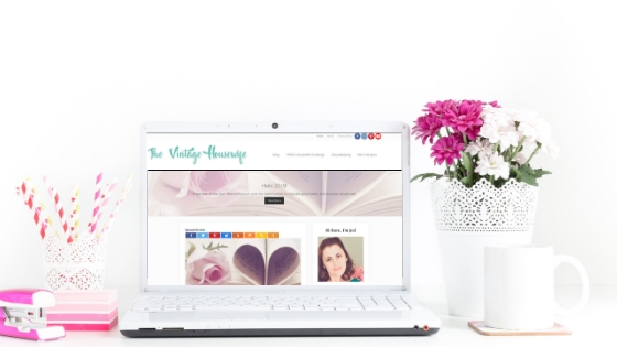 The Vintage Housewife website on a white laptop sitting on a desk with a mug, pink flowers and pink office supplies.