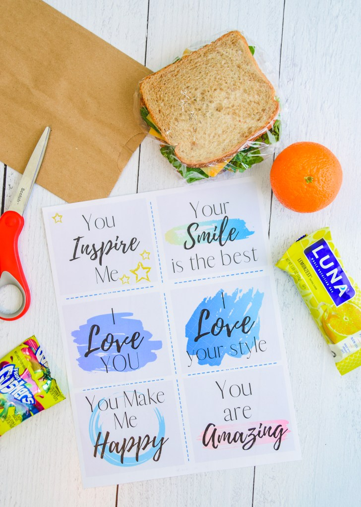 free compliment card printable for kids lunches,  on a white wooden table, surrounded by a sandwich, brown paper bag and kids lunch snacks.
