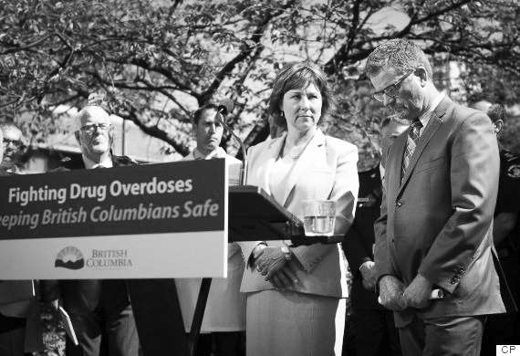 B.C. Health Minister Terry Lake, right, steps to the podium to answer a question as B.C. Premier Christy Clark, centre, watches during a news conference where the government announced the creation of a joint task force on overdose response, in Vancouver, B.C., on Wednesday July 27, 2016. THE CANADIAN PRESS/Darryl Dyck