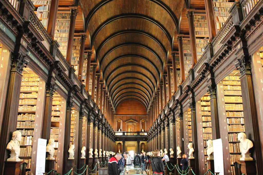 An interior shot of The Long Room in Dublin. A 2 story hallway lined with antique bookshelves and ancient books.