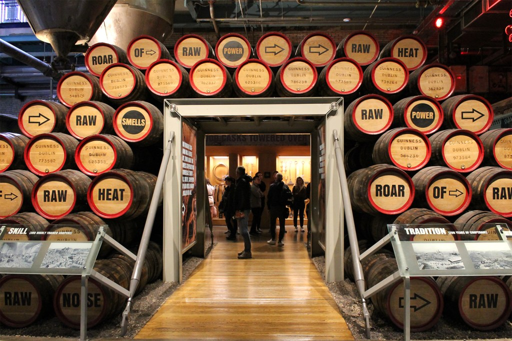 A pass-through is decorated with dozens of wooden barrels stacked around it.