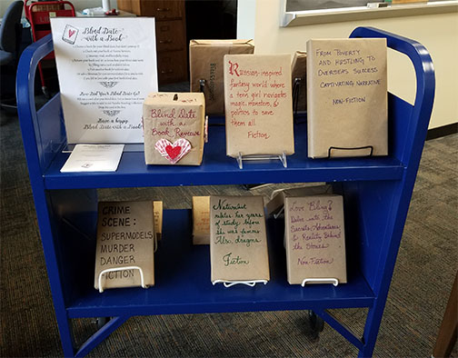 photograph of book cart with books wrapped for blind date with a book