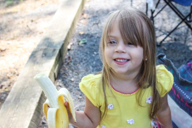 snacks hiking with kids girl eating a banana