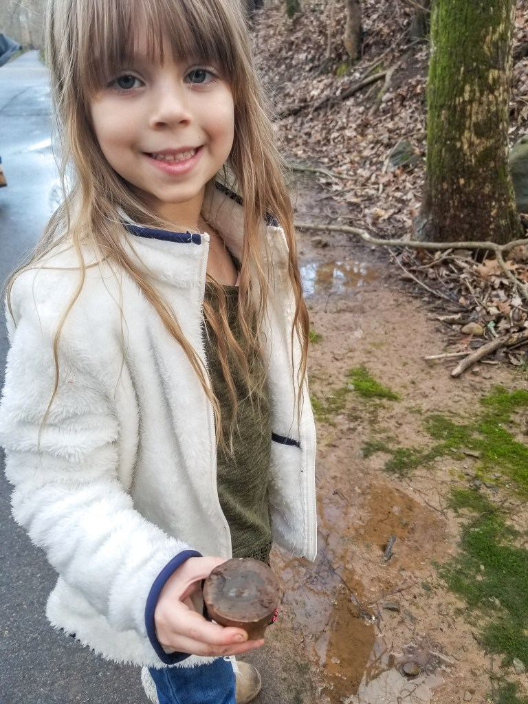 girl holding a rock at the park sensory play
