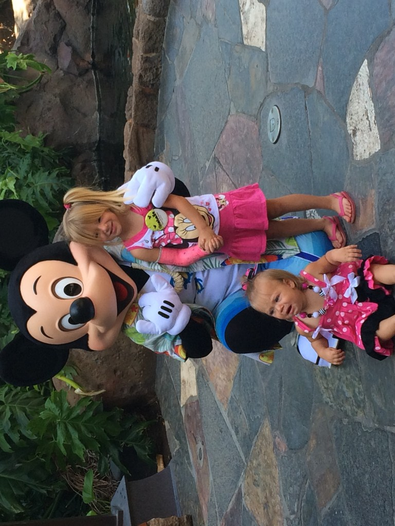 Two kids posing with Mickey Mouse at Aulani Resort in Ko'Olina. Posted on a travel guide that features the best things to do with kids on Oahu, Hawaii.