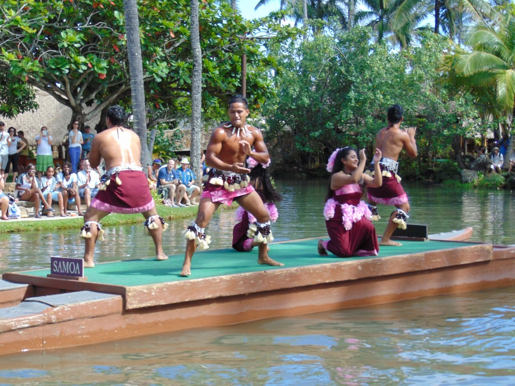 Samoan natives dancing cultural dances on a raft at the Polynesian Cultural Center. Posted on a travel guide that features the best things to do with kids on Oahu, Hawaii.