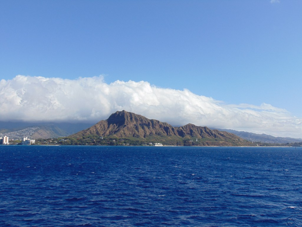 An ocean view of Diamond Head Crater taken during a whale watching boat tour in Honolulu. Posted on a travel guide that features the best things to do with kids on Oahu, Hawaii.