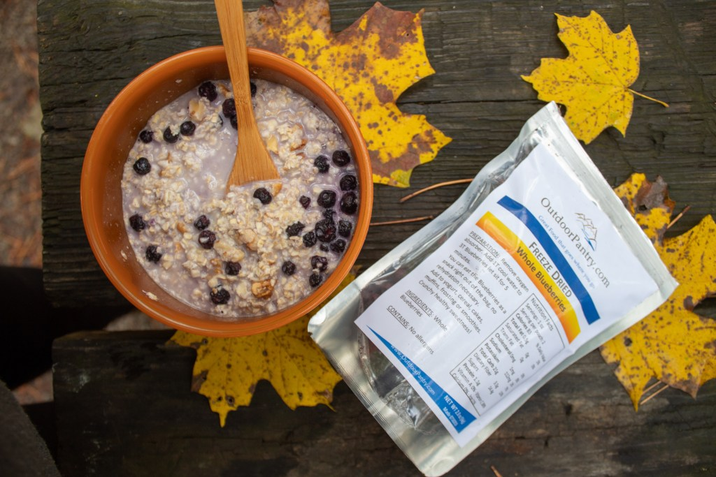 instant oatmeal and dehydrated blueberries cooked during a camping trip in the fall. Orange and yellow leaves outdoors.