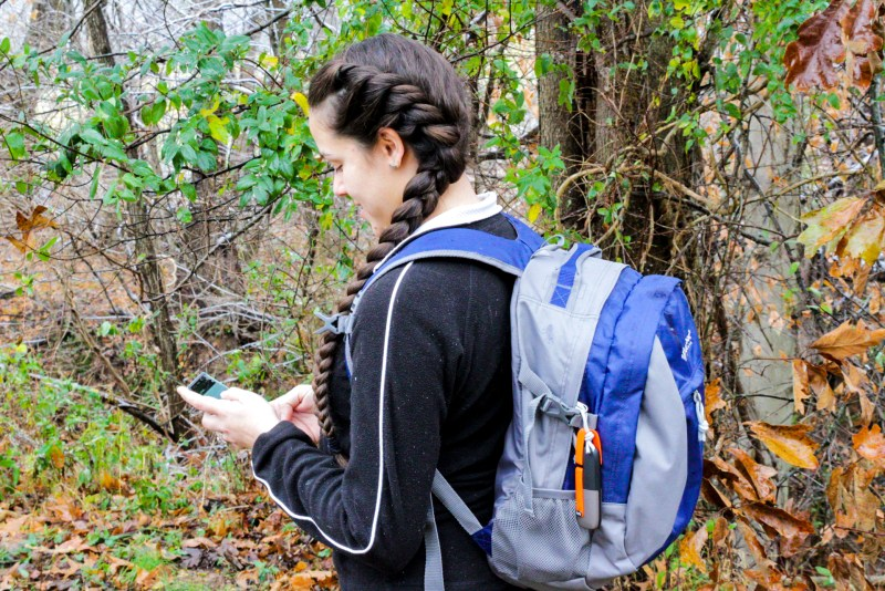Woman using a GoTenna Mesh device to stay in touch with her family during their outdoor adventures such as camping and hiking. Posted on a camping guide talking about camping safety rules for kids follow.
