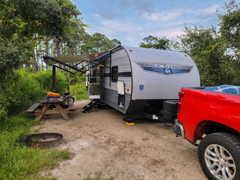 A red chevy silverado attached to a Gulf Stream camper trailer setup at camp. Etiquette for Camper Trailer RV 5th Wheels