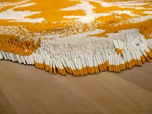Xu Bing used 500000 cigarettes to create a floor art installation resembling a tiger skin rug.