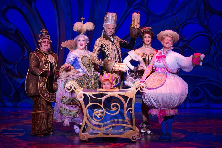 The enchanted objects, featuring as Cogsworth (far left) and as Lumiere (centre).