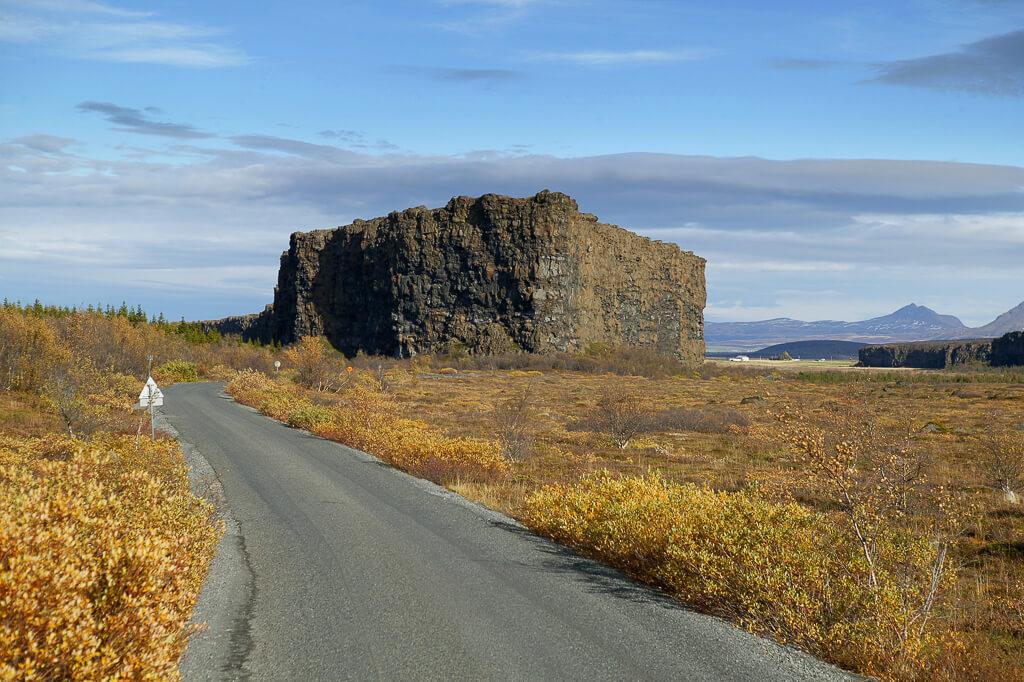 Hoge rots in geel landschap bij asfaltweg.