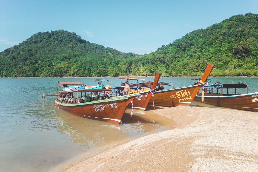 Drie houten longtailboten op strand onderweg naar Koh Phee.