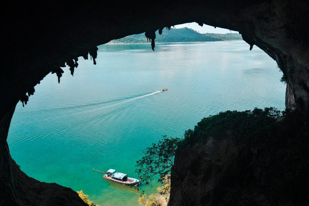 Azuurblauwe zee met twee boten gezien vanuit grot.