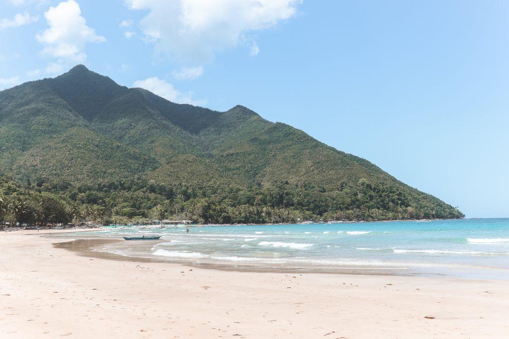 Wit strand en blauw water met groene heuvel op achtergrond in Sabang.