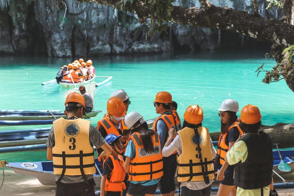 Groep mensen met oranje en gele helmen bij felblauwe rivier.