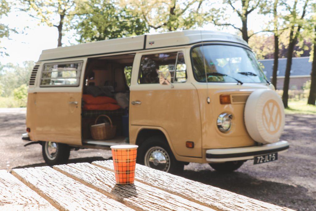Papieren beker met thee op picknicktafel en VW bus op achtergrond.