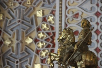 A bronze statue sits in front of a wall with obvious Islamic-inspired geometric patterns