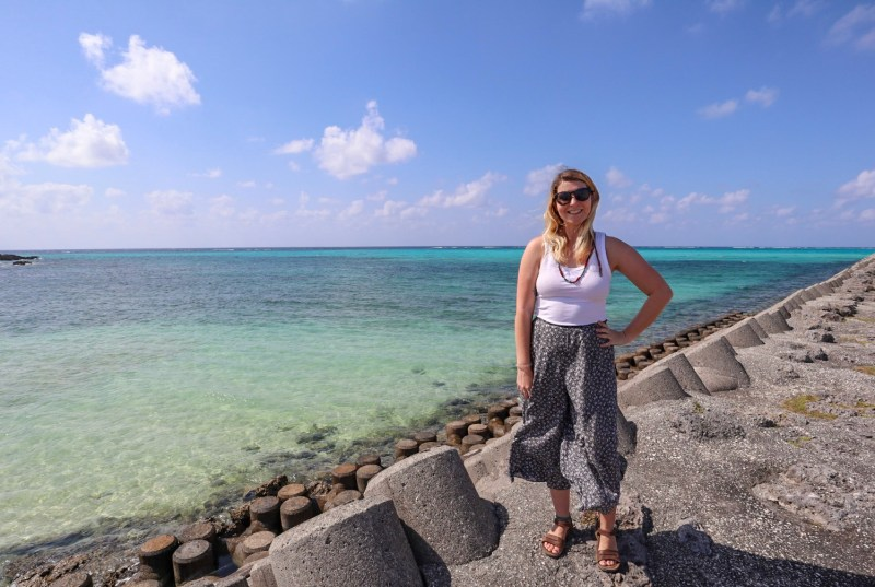 Ellie Quinn with bright blue water behind her | things to do in Miyakojima island