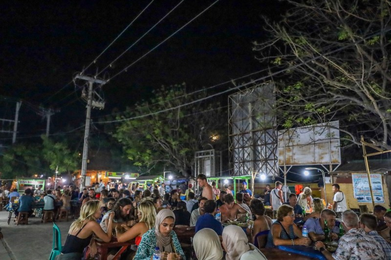 people sat at Gili T night market | itinerary for Gili T