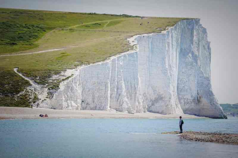 Seven Sisters White Cliffs and Person standing below | Seven Sisters day trip from London by train