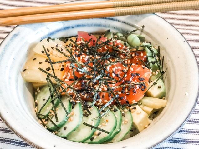 Poke Bowl with chopsticks filled with raw salmon and tuna, sliced cucumbers, chopped pineapple, edamame, sprinkled with sesame seeds and sliced nori