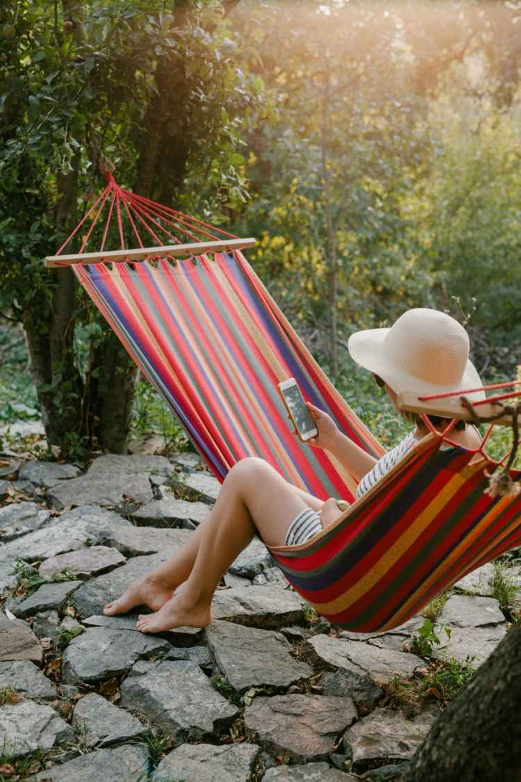 woman with smartphone sitting on hammock in green garden