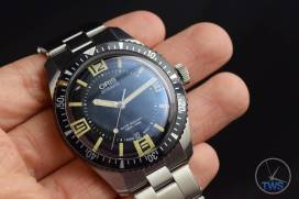 The Oris Divers Sixty-Five (With Metal Bracelet) [01 733 7707 4064-07 8 20 18] held in the hand with a black bacground