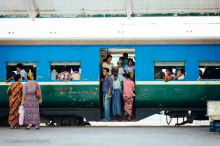 A crowded coach transports passengers in Yangon and it's outlying neighborhoods on the Circular Train. Myanmar, May 2014.
