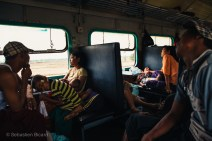 Parents and children get some rest on the hard seats of the Ordinary Class train. Myanmar, May 2014.
