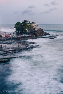 The sacred temple in the surf: Tanah Lot stands off the cost of Bali and welcomes thousands of Hindu pilgrims for the biannual Piodalan Anniversary at sunset. Indonesia, June 2014.