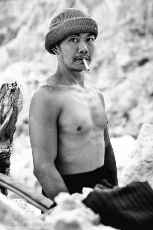 One of the sulphur miners in Kawa Ijen crater takes a break from carrying his 200lb load. Java, Indonesia, June 2014.