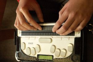 A woman's hands poised on a Braille translator keyboard. This device is used by WeCo for digital accessibility.