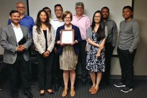 Group of smiling individuals standing together in a conference room. WeCo President, Lynn Wehrman, is holding a certificate and standing at the center.