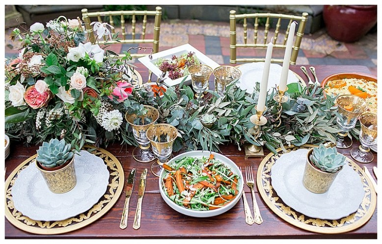 A table is set with gold cutlery and plates, and decorated with a foliage table runner