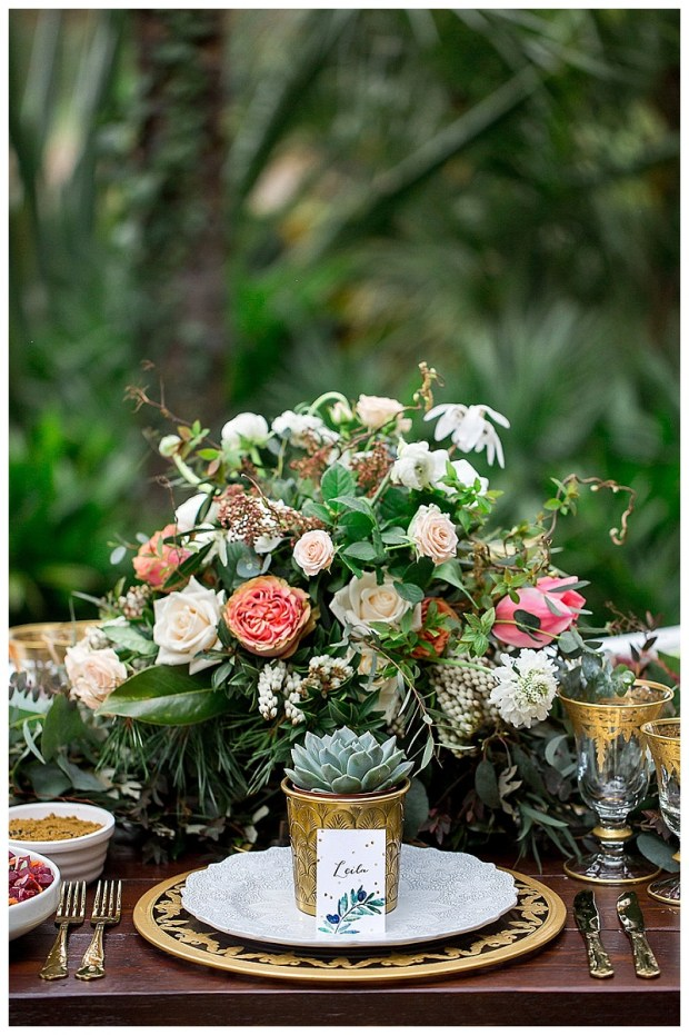 A floral centrepiece from Cherfold Cottage Flowers sits amid luxe gold tableware.