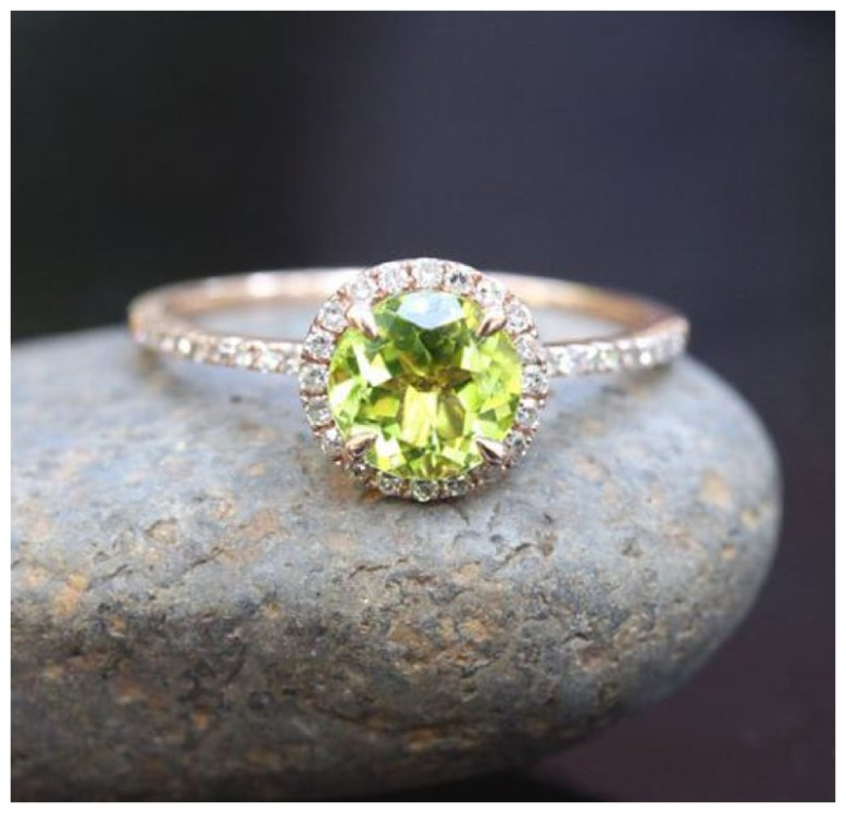 Peridot and diamond engagement ring sits on a stone