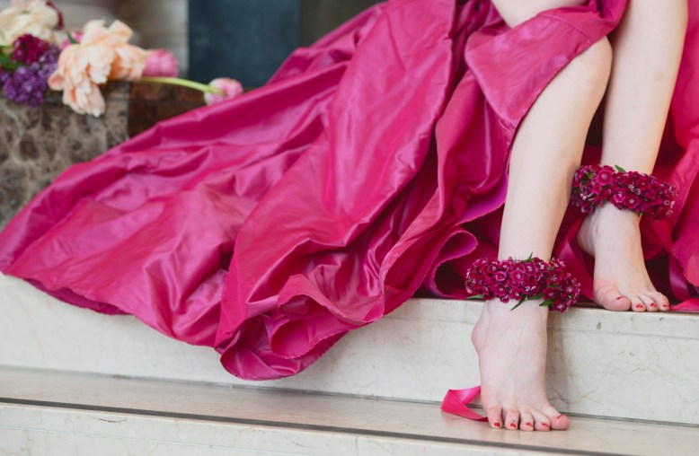 The Language of Flowers: A bride wears a full magenta skirt and sits with bare feet and ankle cuffs made from Sweet William