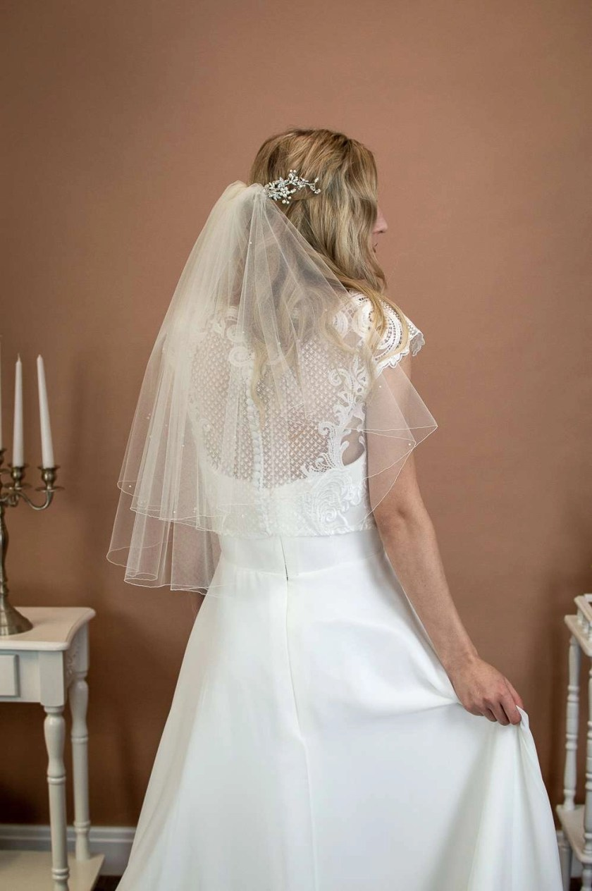 Abigail - two tier short elbow length wedding veil with scattered crystas and pearls on a bride