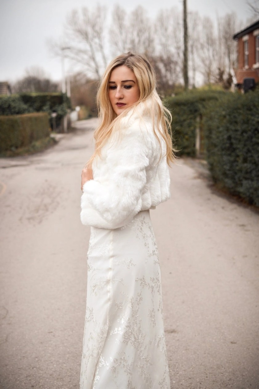 BB20 – bridal jacket with collar and full sleeves in ivory faux fur on blonde bride with hair down on country lane 6