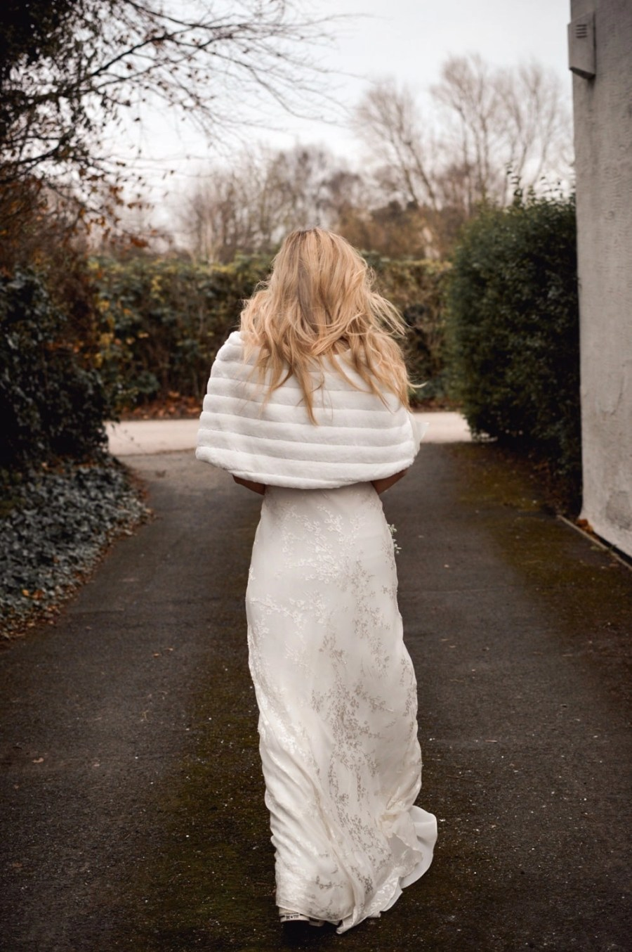 BB22 – faux fur bridal cape wrap shrug with a pretty satin bow on blonde bride with hair down back view walking